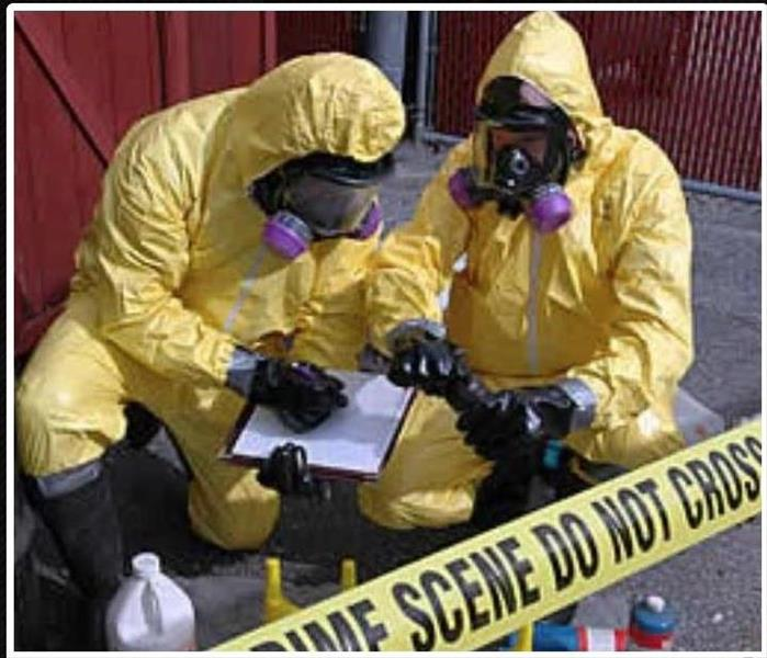 Two technicians with yellow suits and masks collecting samples with a caution tape surrounding them
