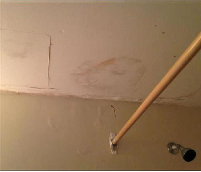 Water stained ceiling with a shower head and a old curtain metal rod attached to the wall