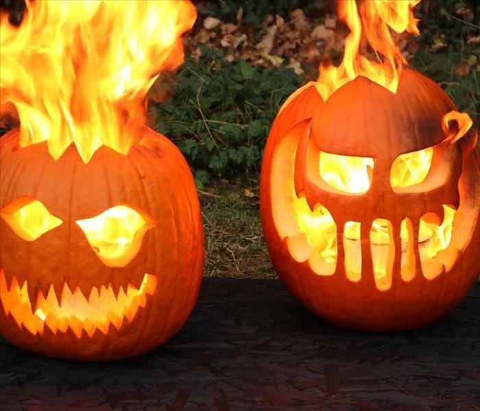 Two carved pumpkins that are up in flames.